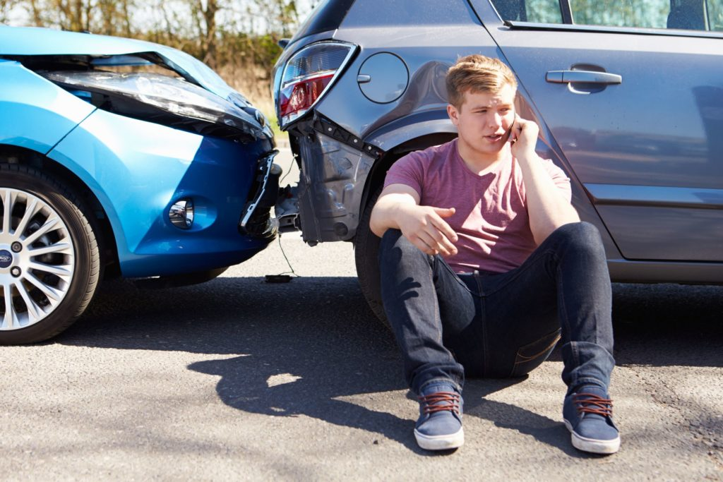 man sitting by his car of the scene of a car crash